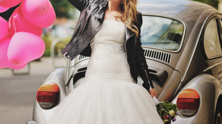 bride wearing leather jacket in front of a car